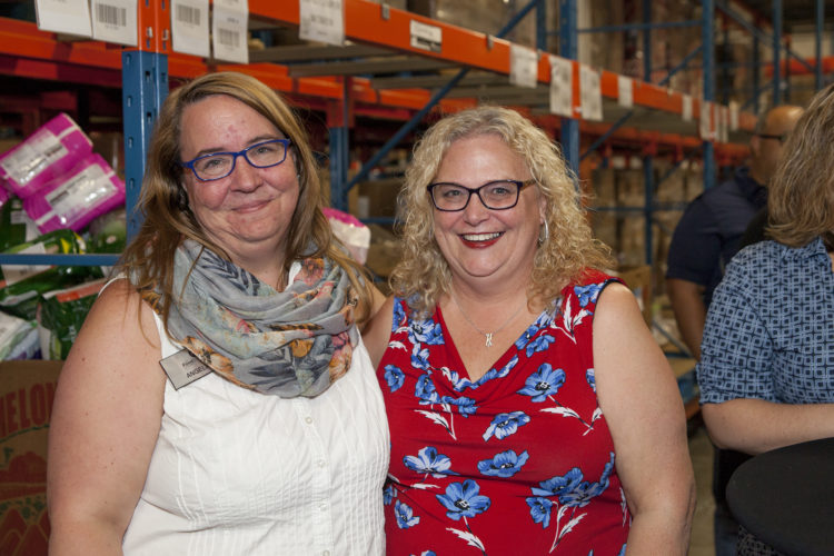 A staff member and volunteer in the warehouse
