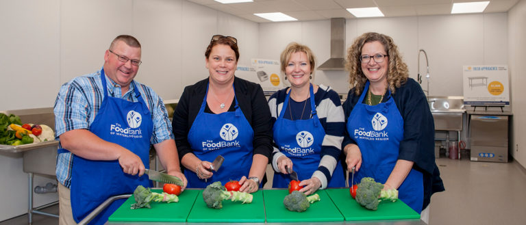 Representative of The Food Bank of Waterloo Region and supporters cutting the first vegetables of the Fresh Approaches Food Centre