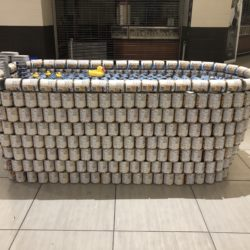 A structure made of cans of a bath tub with yellow ducks floating