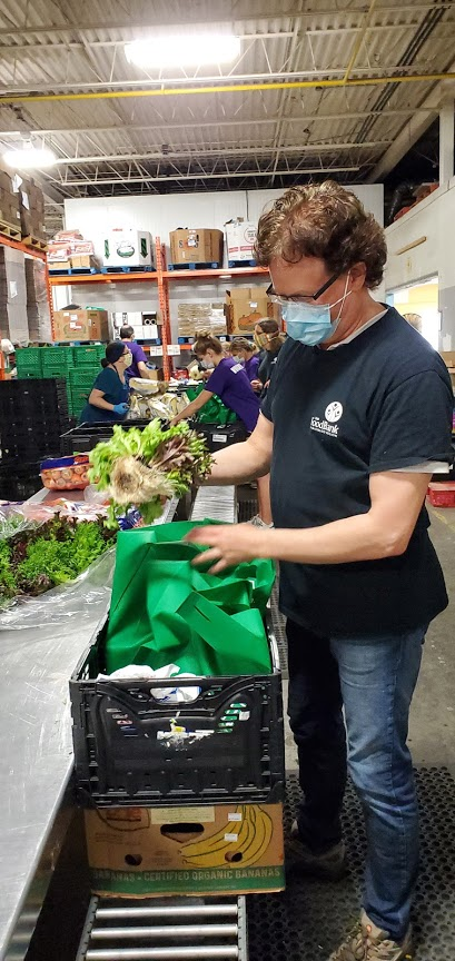 A volunteer is preparing a perishable food hamper in The Food Bank warehouse during the COVID-19 pandemic.